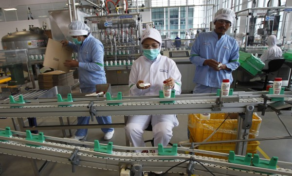 A worker checks a L'Oreal product before it is packed at the company's largest factory in Jababeka Industrial Estate in Cikarang